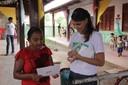 Servidora do MPF entrega fôlder didático sobre as eleições a moradora da comunidade